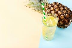 Pi?a y jugo con hielo en un vidrio, en un fondo amarillo azul Humor del verano, espacio de la copia imagenes de archivo
