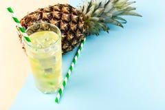 Pi?a y jugo con hielo en un vidrio, en un fondo amarillo azul Humor del verano, espacio de la copia fotos de archivo libres de regalías