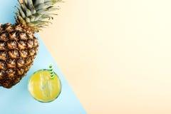 Pi?a y jugo con hielo en un vidrio, en un fondo amarillo azul Humor del verano, espacio de la copia foto de archivo libre de regalías
