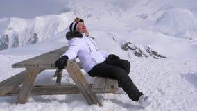 Piacere dello sciatore della donna rilassarsi nelle montagne su Sunny Day, sedentesi sul banco stock footage