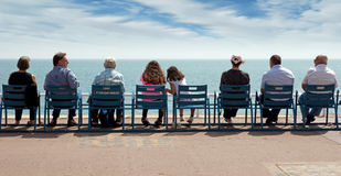 Piacevole - la gente si siede sulle sedie Immagini Stock
