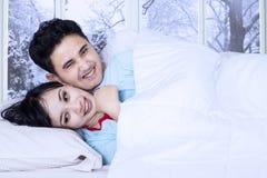 Piada feliz dos pares na cama Fotografia de Stock