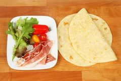 Piada ingredients on a board. Piada ingredients on a wooden chopping board, top view Royalty Free Stock Photos