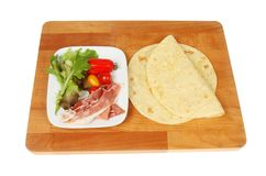 Piadin ingredients on a board. Piadini ingredients on a wooden chopping board isolated against white Stock Image