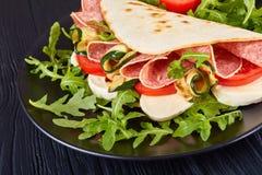 Piadina με τη μοτσαρέλα, ντομάτα, σαλάμι, κολοκύθια Στοκ Φωτογραφίες