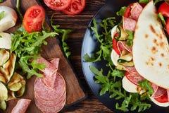 Piadina με τη μοτσαρέλα, ντομάτα, φέτες σαλαμιού Στοκ Φωτογραφίες