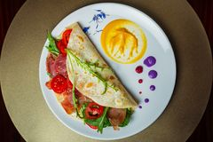 Piadina with chamoon, mozzarella, cherry tomatoes and arca on a. Plate Royalty Free Stock Image