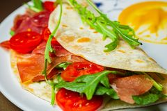 Piadina with chamoon, mozzarella, cherry tomatoes and arca on a. Plate Royalty Free Stock Photos