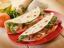 Piadina with ham and arugula Stock Photos