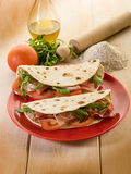 Piadina with ham and arugula. Piadina with ham arugula and tomatoes, typical italian sandwich stock images