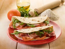 Piadina with ham and arugula. Piadina with ham arugula and tomatoes, typical italian sandwich stock image