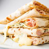 Piadina sandwich. Piadina( Italian flat-bread, typically prepared in the Romagna region)  slices with cheese, ham and arugula Stock Photo