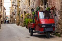 Piaggio Ape at the empty street. Piaggio Ape standing at the empty street of old italian town royalty free stock photo
