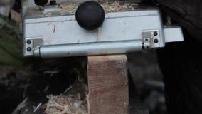 Piallatrice di legno di uso dei lavoratori dell'officina I chip volano nel lato diverso dalla piallatrice video d archivio