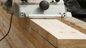 Piallatrice di legno di uso dei lavoratori dell'officina I chip volano nel lato diverso dalla piallatrice 4K video d archivio