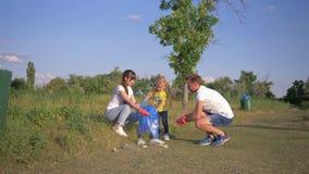 Pianeta di risparmio, giovane famiglia con le cure della ragazza del bambino circa ecologia ambientale e raccogliere rifiuti di p archivi video
