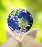 Pianeta Terra della tenuta in mani contro il backgr della molla dell'erba verde Fotografia Stock