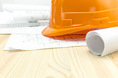 Piani architettonici con il casco di sicurezza arancio immagine stock