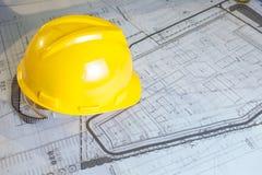 Piani della costruzione con il casco giallo Fotografia Stock Libera da Diritti