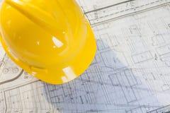 Piani della costruzione con il casco giallo Fotografia Stock