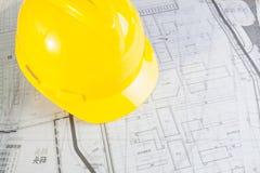 Piani della costruzione con il casco giallo Immagine Stock
