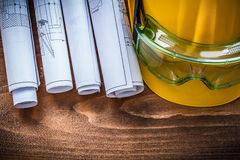 Piani e casco della costruzione degli occhiali di protezione sul bordo di legno marrone Fotografia Stock