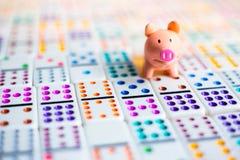 Pianificazione aziendale con il porcellino salvadanaio per il gioco di risparmio di domino e dei soldi Fotografia Stock Libera da Diritti