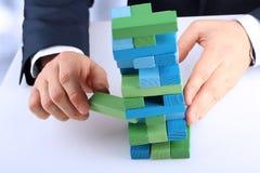 Pianificazione, rischio e strategia nell'affare, uomo d'affari che esce un blocco di legno da una torre Immagini Stock
