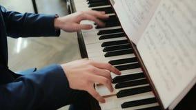 Pianist in blauwe kostuumspelen snel op de piano stock videobeelden