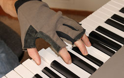 A pianist fights the chill of winter by playing with fingerless gloves. A pianist strikes a chord on the piano while wearing fingerless gloves to keep his hands Stock Photos