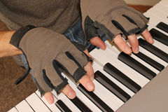 A pianist keeps fights the chill of winter by playing with fingerless gloves. Stock Image