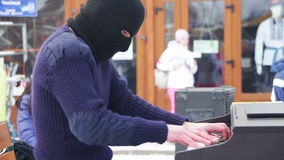 Pianist in the mask plays the piano on the street. A man in a black mask plays piano sitting on a chair in the street among the people during the winter stock footage