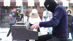 Pianist in the mask plays the piano on the street stock footage