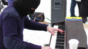Pianist in the mask plays the piano on the street. A man in a black mask plays piano sitting on a chair in the street among the people during the winter stock video footage