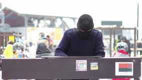 Pianist in the mask plays the piano on the street. A man in a black mask plays piano sitting on a chair in the street among the people during the winter stock video