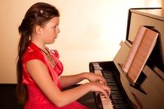 Pianist med det klassiska musikinstrumentet för flygel Pianist med det klassiska musikinstrumentet för flygel leka för flickapian Royaltyfri Foto