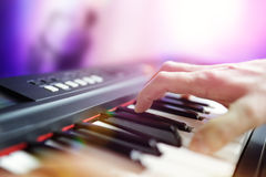 Pianist musician performing live playing keyboard in a band. With saxophone player in background Stock Images