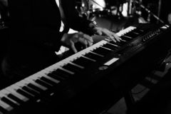 A pianist musician is performing and playing some nice music by using a piano keyboard on a stage at some nightclub or pub with. His band. Black and white photo royalty free stock image