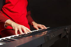 Pianist play the keys of the electronic piano on black background Stock Photos