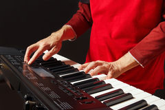 Pianist play the keys of the electronic synth on black background Stock Images