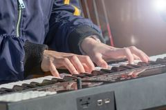 Pianist play the keys of the electronic synth at the outdoor performance royalty free stock image