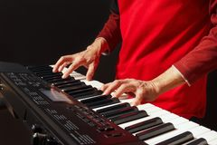 Pianist play the keys of the synth on black background Royalty Free Stock Photography