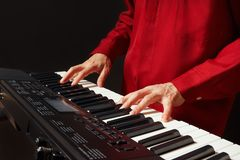 Pianist playing the electronic synth on black background Royalty Free Stock Image