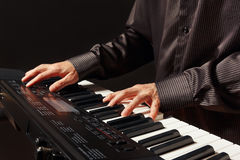 Pianist playing the electronic synthesizer on black background Stock Photography