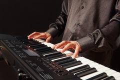 Pianist playing the synth on black background Royalty Free Stock Images