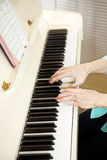 Pianist Plays Church Hymns. Closeup of a church pianists hands as she plays from the hymnal Royalty Free Stock Photography