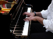 Pianist Plays Jazz Music. Close-up of pianist's hands during a concert of classical jazz music with a grand coda piano on black background Royalty Free Stock Images