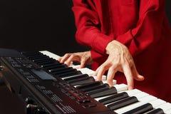 Pianist som spelar det digitala pianot på svart bakgrund Arkivfoto