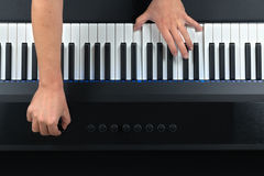 Pianist som spelar det elektriska pianot, medan ändra inställningar Arkivbild
