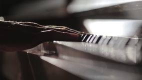 Pianist touching piano keyboard with his fingers.